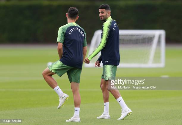 Manchester City's Riyad Mahrez talks with Phil Foden during training at Manchester City Football Academy on July 16 2018 in Manchester England