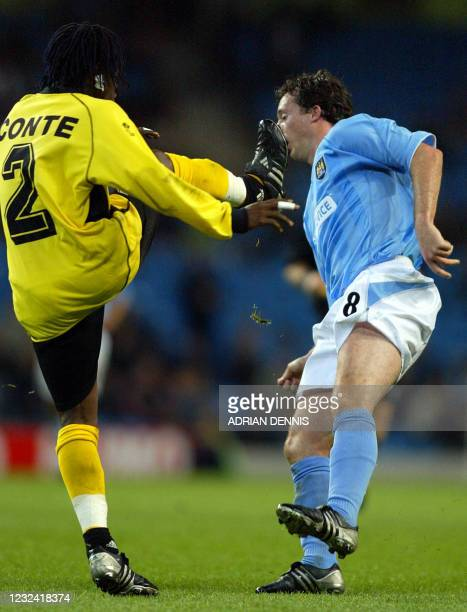 Manchester City's Robbie Fowler takes evasive action to avoid the boot of Ibrahima Conte Sory of Sporting Lokeren during the UEFA Cup First Round...