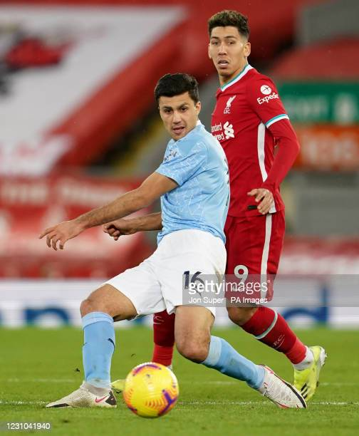 Manchester City's Rodri and Liverpool's Roberto Firmino during the Premier League match at Anfield, Liverpool. Picture date: Sunday February 7, 2021.