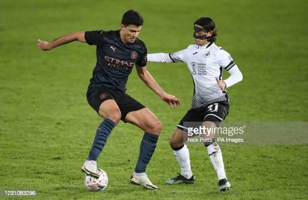 Manchester City's Rodri and Swansea City's Yan Dhanda battle for the ball during the Emirates FA Cup fifth round match at Liberty Stadium, Swansea....