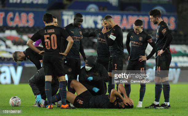 Manchester City's Rodri is treated after a challenge from Swansea City's Yan Dhanda during The Emirates FA Cup Fifth Round match between Swansea City...