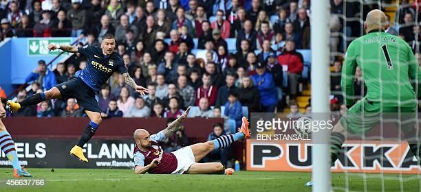 Manchester City's Serbian defender Aleksandar Kolarov has an unsuccessful shot past Aston Villa's Swiss defender Philippe Senderos during the English...