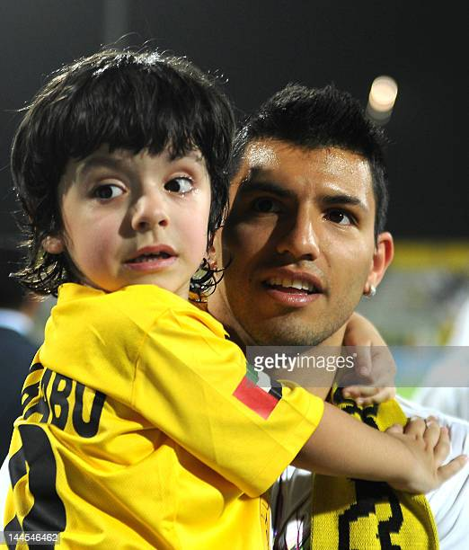 Manchester City's Sergio Aguero son in law of AlWasl club's Argentinian head coach Diego Maradona holds his son Benjamin as they attend a Gulf...
