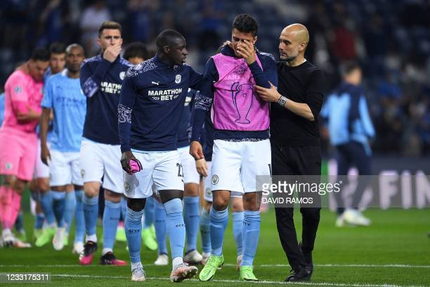 Manchester City's Spanish coach Josep Guardiola and Manchester City's players react at the end of the UEFA Champions League final football match...