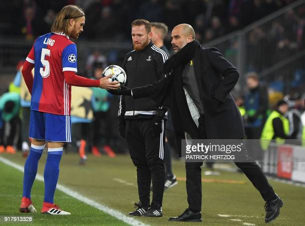Manchester City's Spanish head coach Pep Guardiola hands the ball to Basel's Swiss defender Michael Lang during the UEFA Champions League round of 16...