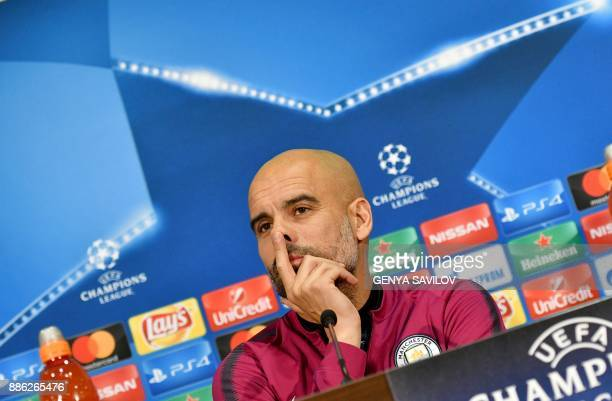 Manchester City's Spanish head coach Pep Guardiola listens to journalists during a press conference in Kharkiv on December 5 on the eve of the UEFA...
