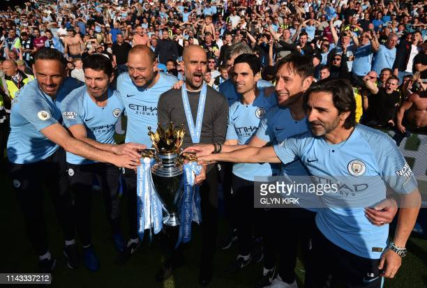 TOPSHOT Manchester City's Spanish manager Pep Guardiola and his backroom staff pose with the Premier League trophy after their 41 victory in the...