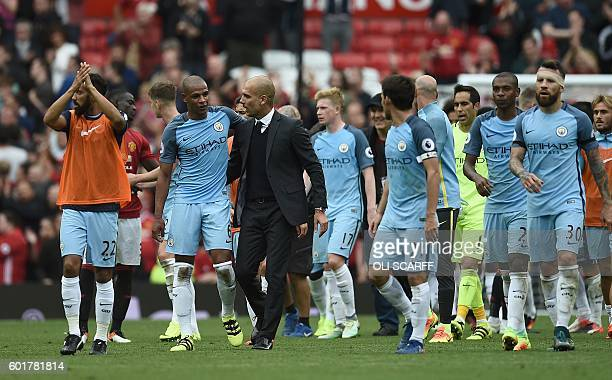 Manchester City's Spanish manager Pep Guardiola and his players celebrate on the pitch after the English Premier League football match between...