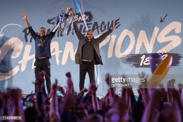 Manchester City's Spanish manager Pep Guardiola and Manchester City's Belgian defender Vincent Kompany show the Premier League trophy to supporters...