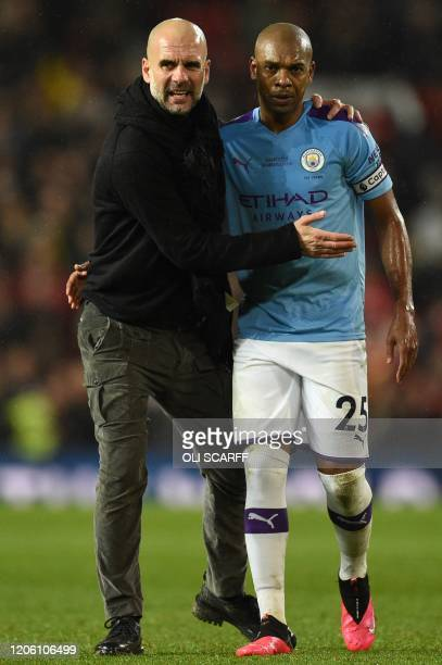 Manchester City's Spanish manager Pep Guardiola and Manchester City's Brazilian midfielder Fernandinho react after losing the English Premier League...