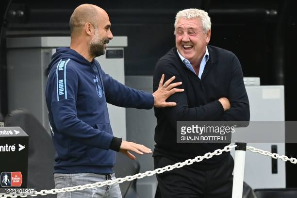 Manchester City's Spanish manager Pep Guardiola and Newcastle United's English head coach Steve Bruce share a joke before kick off of the English FA...