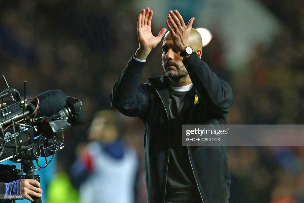 Manchester City's Spanish manager Pep Guardiola applauds supporters on the pitch as they celebrate after the English League Cup semi-final, second leg football match between Bristol City and Manchester City at Ashton Gate Stadium in Bristol, south-west England on January 23, 2018. Manchester City won the game 3-2, (5-3 on aggregate). / AFP PHOTO / Geoff CADDICK / RESTRICTED TO EDITORIAL USE. No use with unauthorized audio, video, data, fixture lists, club/league logos or 'live' services. Online in-match use limited to 75 images, no video emulation. No use in betting, games or single club/league/player publications. /