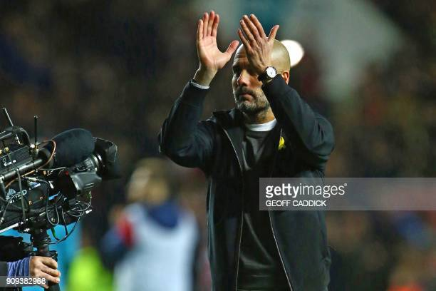Manchester City's Spanish manager Pep Guardiola applauds supporters on the pitch as they celebrate after the English League Cup semifinal second leg...