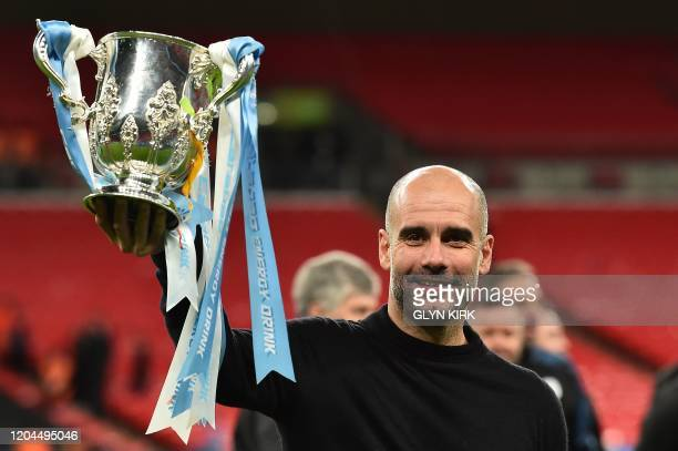 Manchester City's Spanish manager Pep Guardiola celebrates with the trophy on the pitch after the English League Cup final football match between...
