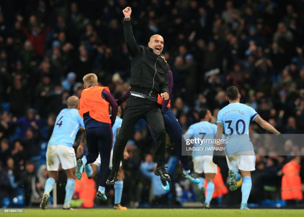 TOPSHOT - Manchester City's Spanish manager Pep Guardiola (C) celebrsates after Manchester City's English midfielder Raheem Sterling scores his team's second goal during the English Premier League football match between Manchester City and Southampton at the Etihad Stadium in Manchester, north west England, on November 29, 2017. Manchester City won the match 2-1. / AFP PHOTO / Lindsey PARNABY / RESTRICTED TO EDITORIAL USE. No use with unauthorized audio, video, data, fixture lists, club/league logos or 'live' services. Online in-match use limited to 75 images, no video emulation. No use in betting, games or single club/league/player publications. /