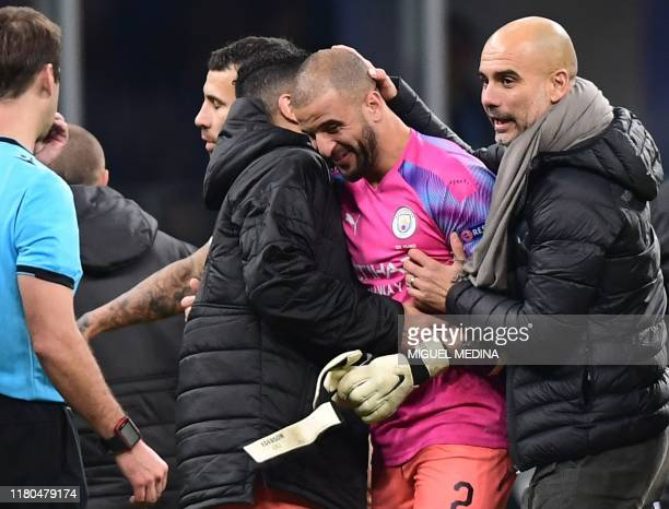 Manchester City's Spanish manager Pep Guardiola congratulates Manchester City's English defender Kyle Walker who replaced the team's goalkeeper at...