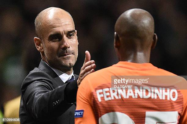 Manchester City's Spanish manager Pep Guardiola congratulates Manchester City's Brazilian midfielder Fernandinho following the UEFA Champions League...