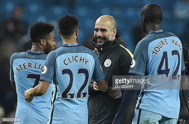 Manchester City's Spanish manager Pep Guardiola congratulates Manchester City's English midfielder Raheem Sterling Manchester City's French defender...