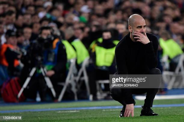 Manchester City's Spanish manager Pep Guardiola crouches on the sideline during the UEFA Champions League round of 16 firstleg football match between...