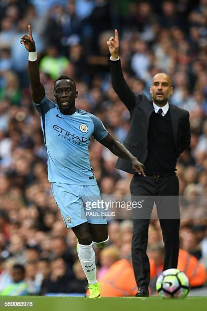 Manchester City's Spanish manager Pep Guardiola gesture behind Manchester City's French defender Bacary Sagna uring the English Premier League...