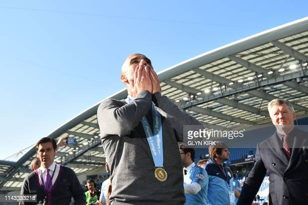 Manchester City's Spanish manager Pep Guardiola gestures to supporters as they celebrate after their 41 victory in the English Premier League...