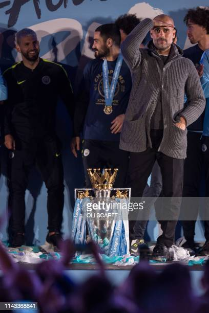 Manchester City's Spanish manager Pep Guardiola gets ready to show the Premier League trophy to supporters outside the Etihad Stadium in Manchester...
