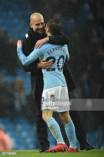Manchester City's Spanish manager Pep Guardiola greets Manchester City's Portuguese midfielder Bernardo Silva after during the English Premier League...