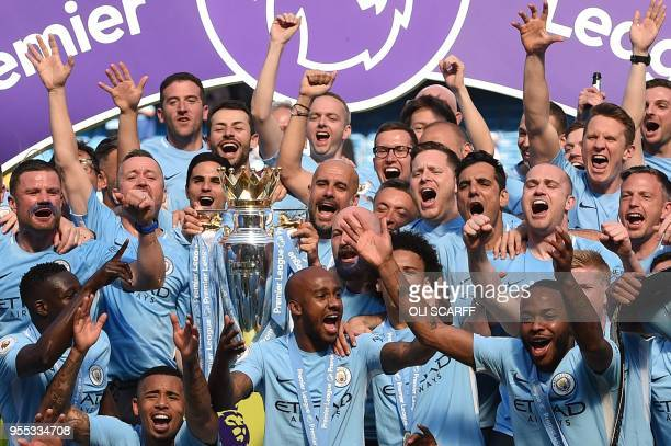 Manchester City's Spanish manager Pep Guardiola holds the Premier League trophy on the pitch with Manchester City players after the English Premier...