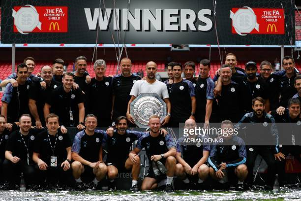 Manchester City's Spanish manager Pep Guardiola holds the trophy as he poses with his staff after winning the English FA Community Shield football...