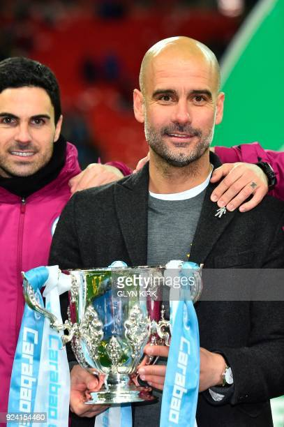 Manchester City's Spanish manager Pep Guardiola holds the trophy as he poses for a photograph as Manchester city players celebrate their victory in...