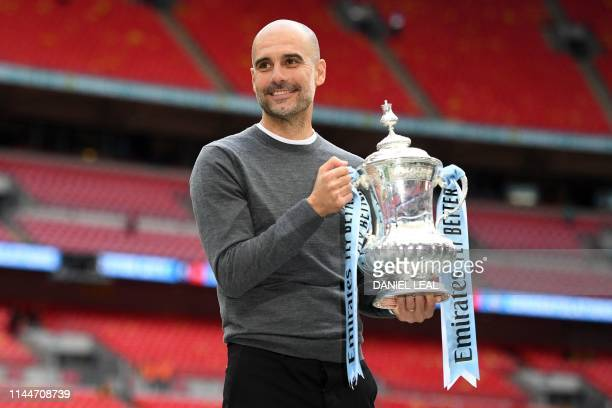 Manchester City's Spanish manager Pep Guardiola holds the winner's trophy as the team celebrates victory after the English FA Cup final football...
