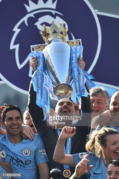 Manchester City's Spanish manager Pep Guardiola holds up the Premier League trophy after their 41 victory in the English Premier League football...