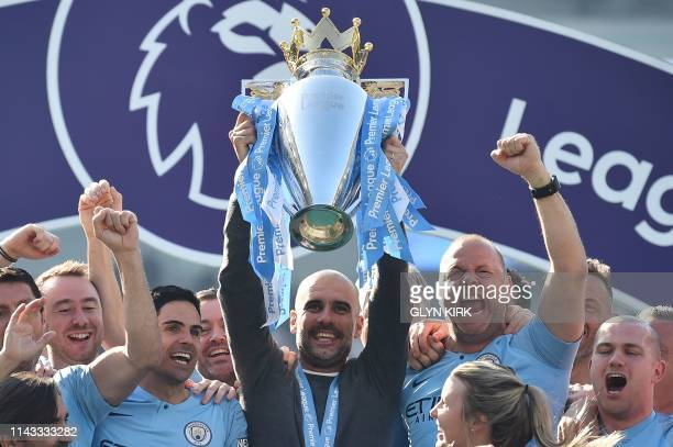 TOPSHOT Manchester City's Spanish manager Pep Guardiola holds up the Premier League trophy as he's surrounded by his staff after their 41 victory in...