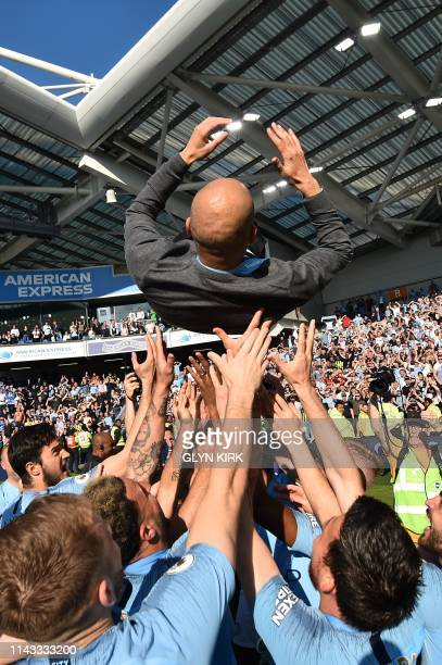 Manchester City's Spanish manager Pep Guardiola is thrown into the air by his players as they celebrate after their 41 victory in the English Premier...