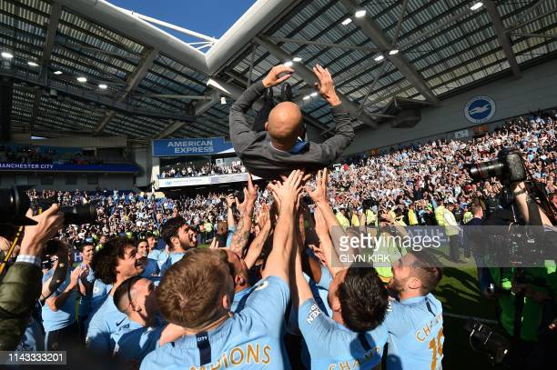 TOPSHOT Manchester City's Spanish manager Pep Guardiola is thrown into the air by his players as they celebrate after their 41 victory in the English...