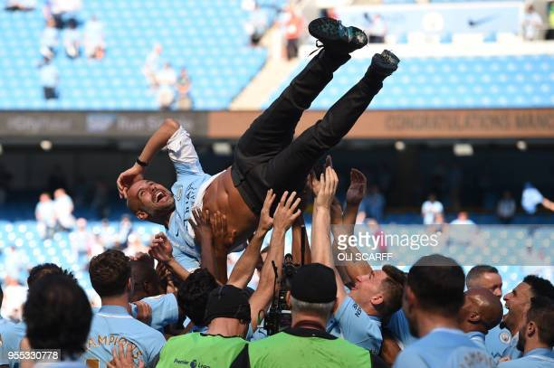 TOPSHOT Manchester City's Spanish manager Pep Guardiola is tossed by Manchester City players during the trophy ceremony after the English Premier...