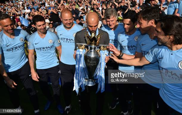 Manchester City's Spanish manager Pep Guardiola kisses the Premier League trophy as he poses with his backroom staff after their 41 victory in the...
