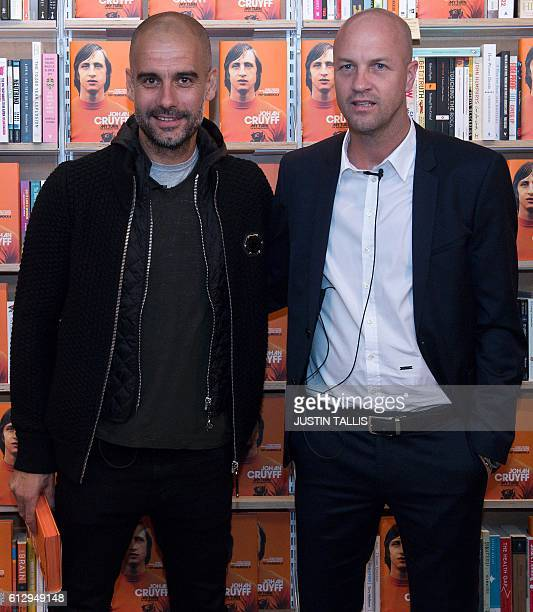 Manchester City's Spanish manager Pep Guardiola poses for a photograph with former Dutch football player and manager Jordi Cruyff at an event to...