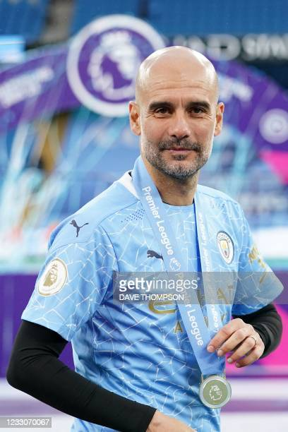 Manchester City's Spanish manager Pep Guardiola poses with his medal during the Premier League trophy award ceremony after the English Premier League...