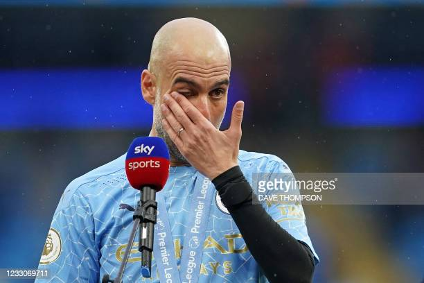Manchester City's Spanish manager Pep Guardiola reacts after the Premier League trophy during the award ceremony after the English Premier League...