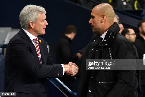 Manchester City's Spanish manager Pep Guardiola shakes hands with Stoke City's Welsh manager Mark Hughes ahead of the English Premier League football...