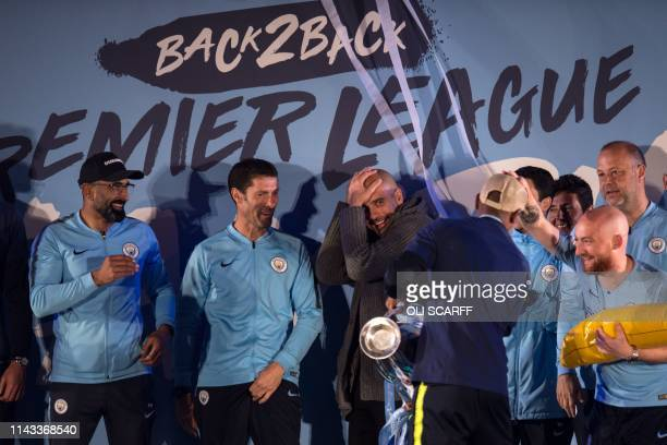 Manchester City's Spanish manager Pep Guardiola shares a joke with his players and coaching staff as they show the Premier League trophy to...