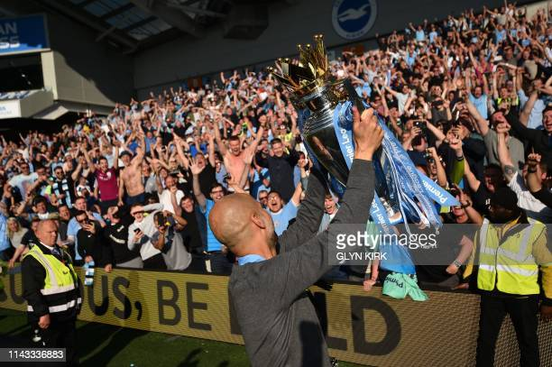 Manchester City's Spanish manager Pep Guardiola shows the Premier League trophy to supporters after their 41 victory in the English Premier League...