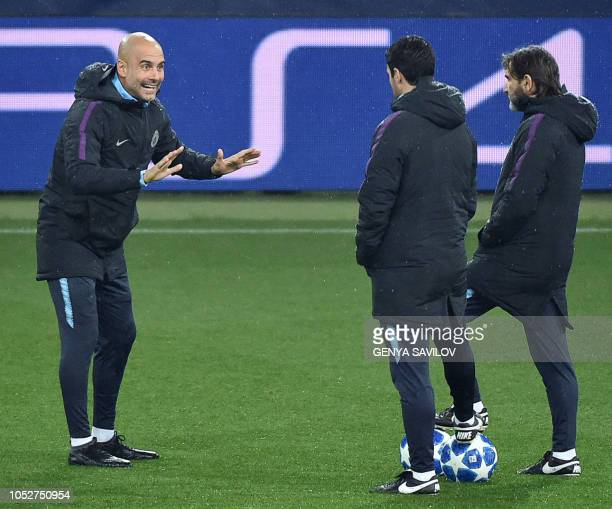 Manchester City's Spanish manager Pep Guardiola speaks with assistants during a training session of Manchester City at the Metallist stadium in...