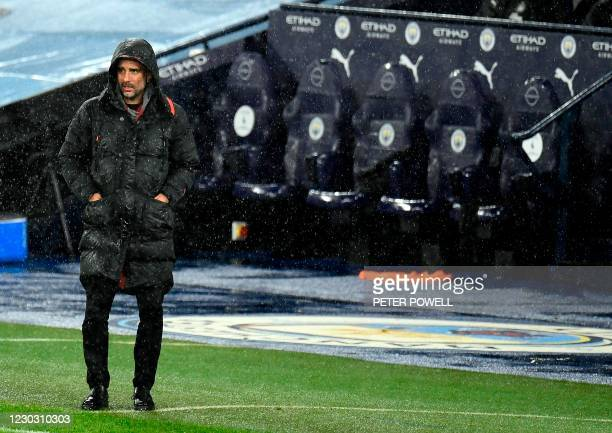 Manchester City's Spanish manager Pep Guardiola stands in the rain during the English Premier League football match between Manchester City and...