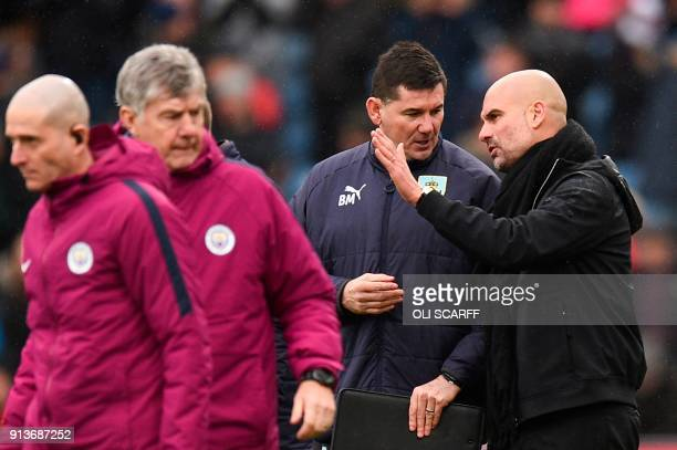 Manchester City's Spanish manager Pep Guardiola talks with Burnley's goalkeeping coach Billy Mercer as they walk off the pitch together at the end of...