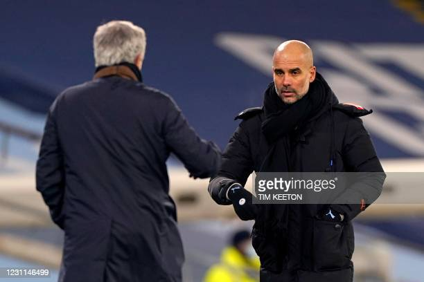 Manchester City's Spanish manager Pep Guardiola taps fists with Tottenham Hotspur's Portuguese head coach Jose Mourinho following the English Premier...
