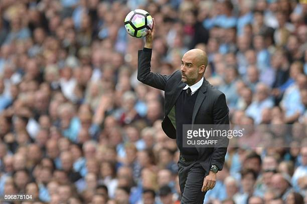 TOPSHOT Manchester City's Spanish manager Pep Guardiola throws the ball back from the touchline during the English Premier League football match...