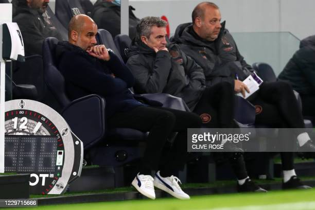 Manchester City's Spanish manager Pep Guardiola watches from his seat during the English Premier League football match between Tottenham Hotspur and...