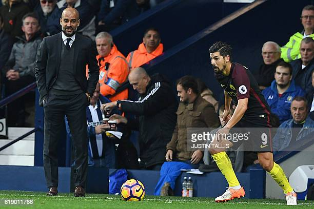 Manchester City's Spanish manager Pep Guardiola watches Manchester City's Spanish midfielder Nolito during the English Premier League football match...